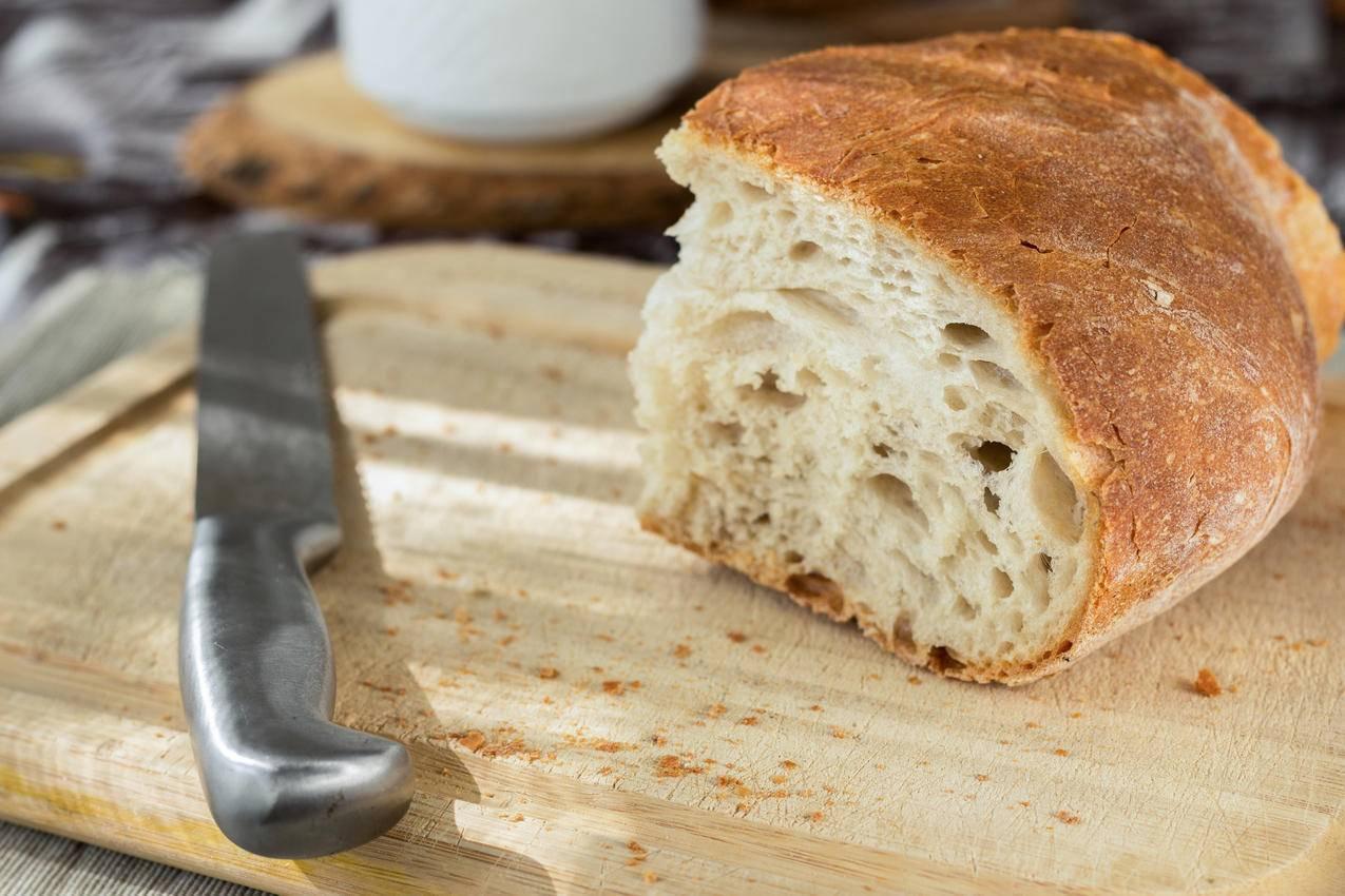 棕色木制砧板上的切片面包和不锈钢刀