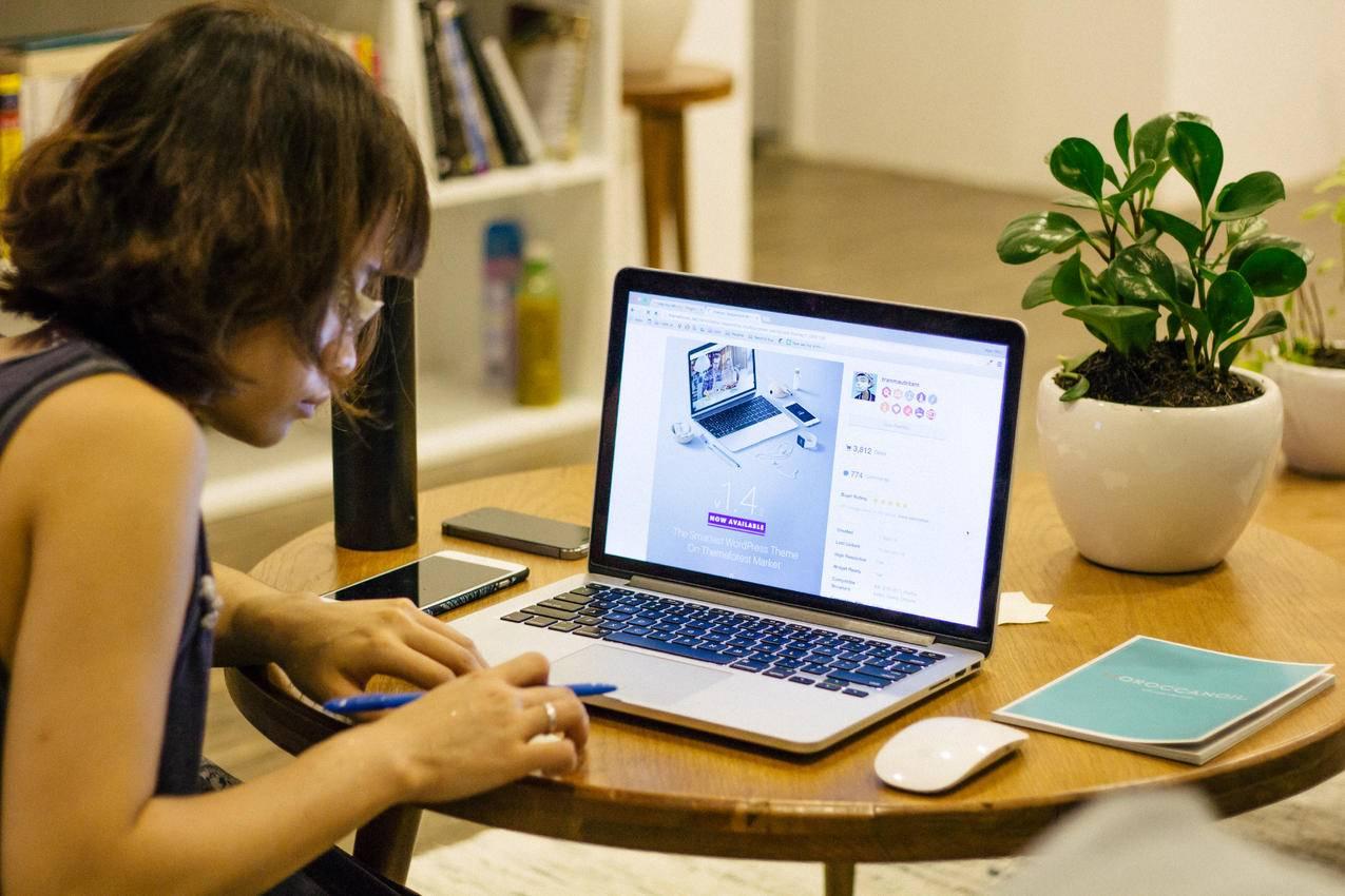 穿着黑木制衬衫的女人在棕色木制圆桌上面对黑色笔记本电脑