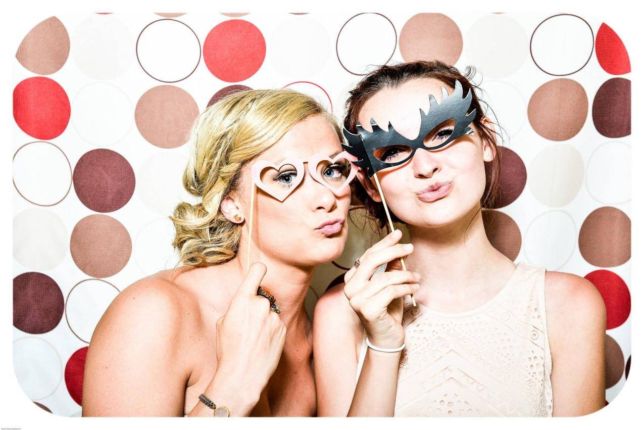 两个女人在照相馆拍照留住黑色和粉红色伪装面具