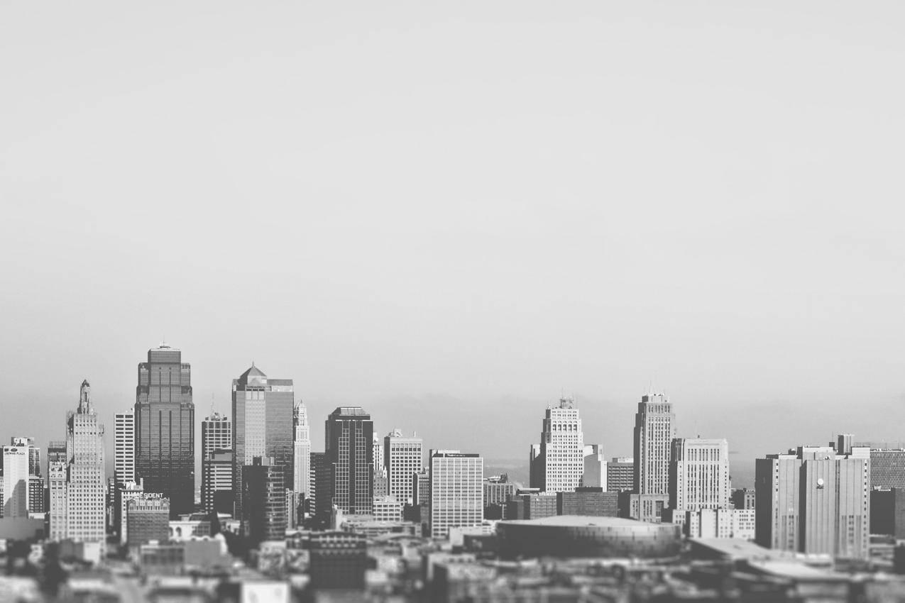 这张黑白照片展示了一个典型的美国城市的商业区和商业区一些中等大小的摩天大楼,一些低矮的建筑物和体育场都是可见的背景似乎有雾