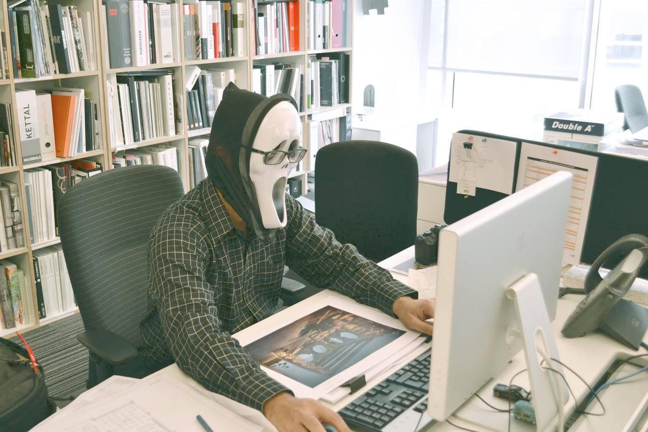 白天面对电脑桌时佩戴尖叫面具和黑色礼服衬衫的人